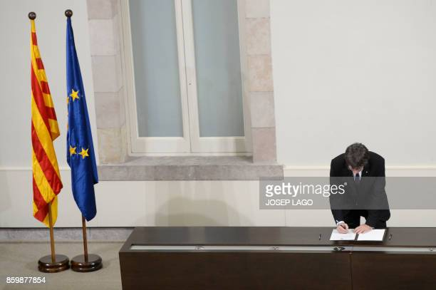 TOPSHOT Catalan regional government president Carles Puigdemont signs a document about the independence of Catalonia at the Catalan regional...