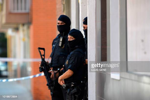 Catalan regional police forces stand guard outside the apartment building of a man who tried to attack a police station in Cornella near the...
