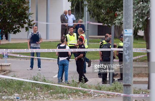 Catalan Regional Police officers inspect surroundings of the morgue in Gava near to Barcelona where a man has shot two local police officers on July...