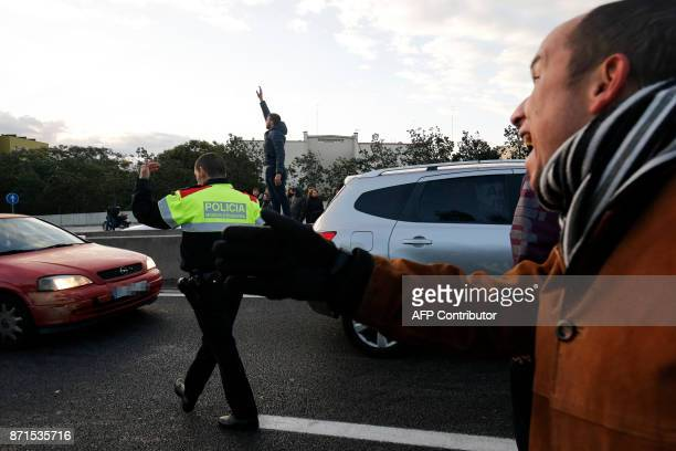 A Catalan regional policeman directs traffic as picketers block the nudo de la Trinidat access road to Barcelona on November 8 2017 as part of a...