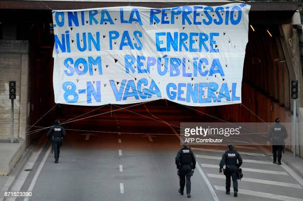 Catalan regional policemen arrive to take down a giant banner reading 'Not a step back against repression We are the republic General strike'...