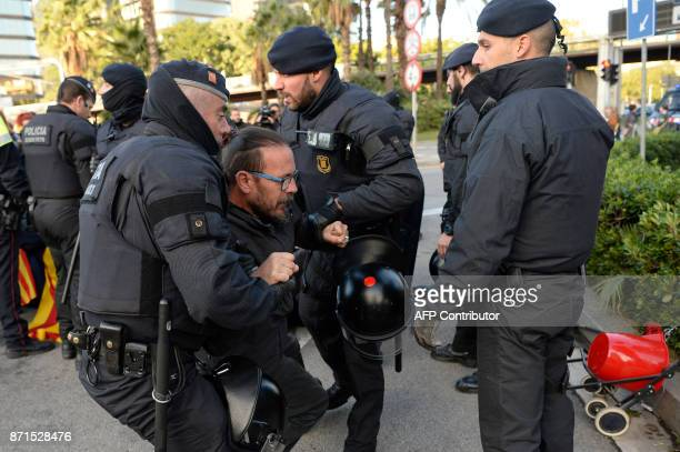 Catalan regional policemen drag a picketer at the Placa Cerda square in Barcelona during a general strike to protest the jailing of eight sacked...