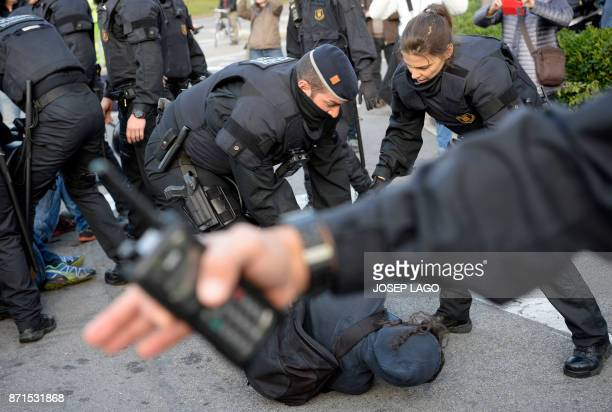 Catalan regional policemen drag a picketer blocking the street at the Placa Cerda square in Barcelona during a general strike to protest the jailing...