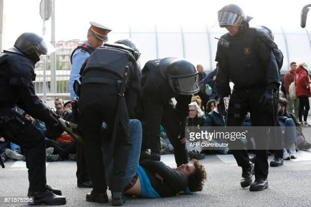Catalan regional policemen drag a picketer blocking the street at the North Bus Station in Barcelona on November 8 2017 as part of a regionwide...