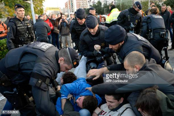 Catalan regional policemen drag picketers at the Placa Cerda square in Barcelona during a general strike to protest the jailing of eight sacked...