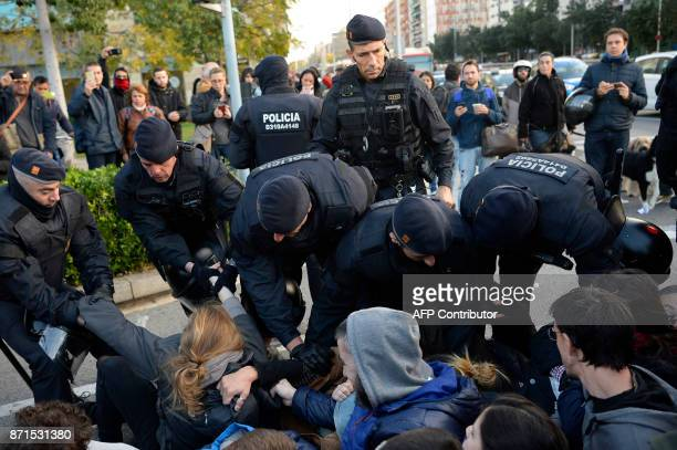 Catalan regional policemen drag picketers blocking the street at the Placa Cerda square in Barcelona during a general strike to protest the jailing...
