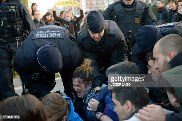 TOPSHOT Catalan regional policemen drag picketers blocking the street at the Placa Cerda square in Barcelona during a general strike to protest the...