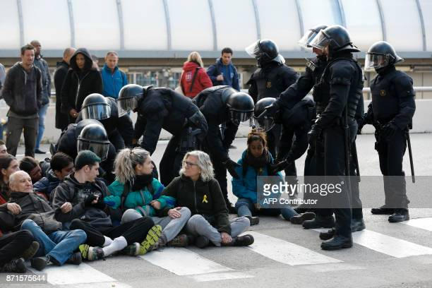 Catalan regional policemen drag picketers blocking the street at the North Bus Station in Barcelona on November 8 2017 as part of a regionwide strike...