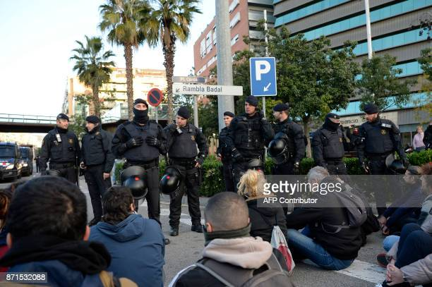 Catalan regional policemen stand in front of picketers blocking the street at the Placa Cerda square in Barcelona during a general strike to protest...