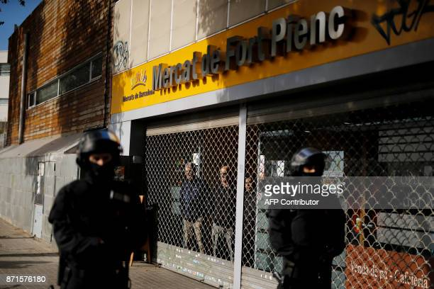 Catalan regional policemen stand near the entrance of the local market Mercat de Fort Pienc in Barcelona on November 8 2017 during a regionwide...