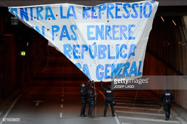TOPSHOT Catalan regional policemen take down a giant banner reading 'Not a step back against repression We are the republic General strike' displayed...