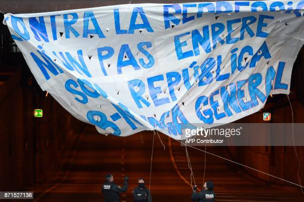Catalan regional policemen take down a giant banner reading 'Not a step back against repression We are the republic General strike' displayed at...