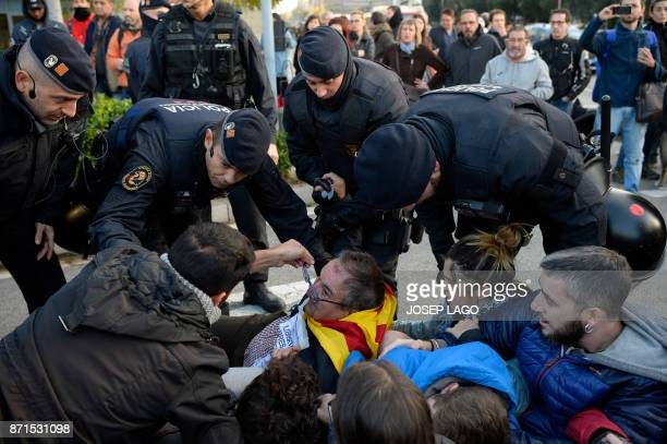TOPSHOT Catalan regional policemen talk to picketers blocking the street at the Placa Cerda square in Barcelona during a general strike to protest...