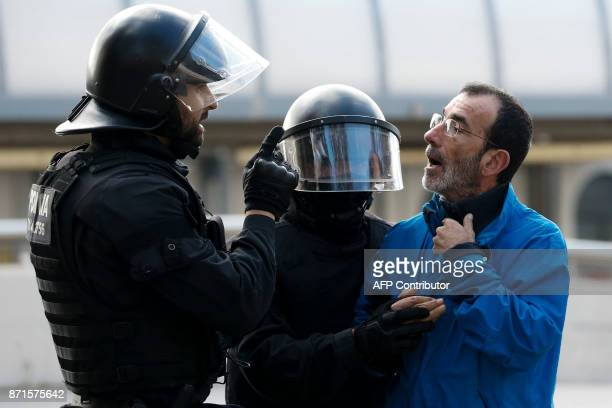Catalan regional policemen talk with a picketer blocking the street at the North Bus Station in Barcelona on November 8 2017 as part of a regionwide...