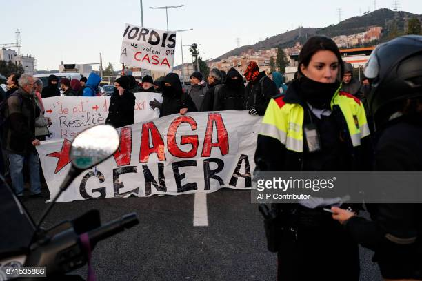 A Catalan regional policewoman talks to rides as picketers block the nudo de la Trinidat access road to Barcelona on November 8 2017 as part of a...