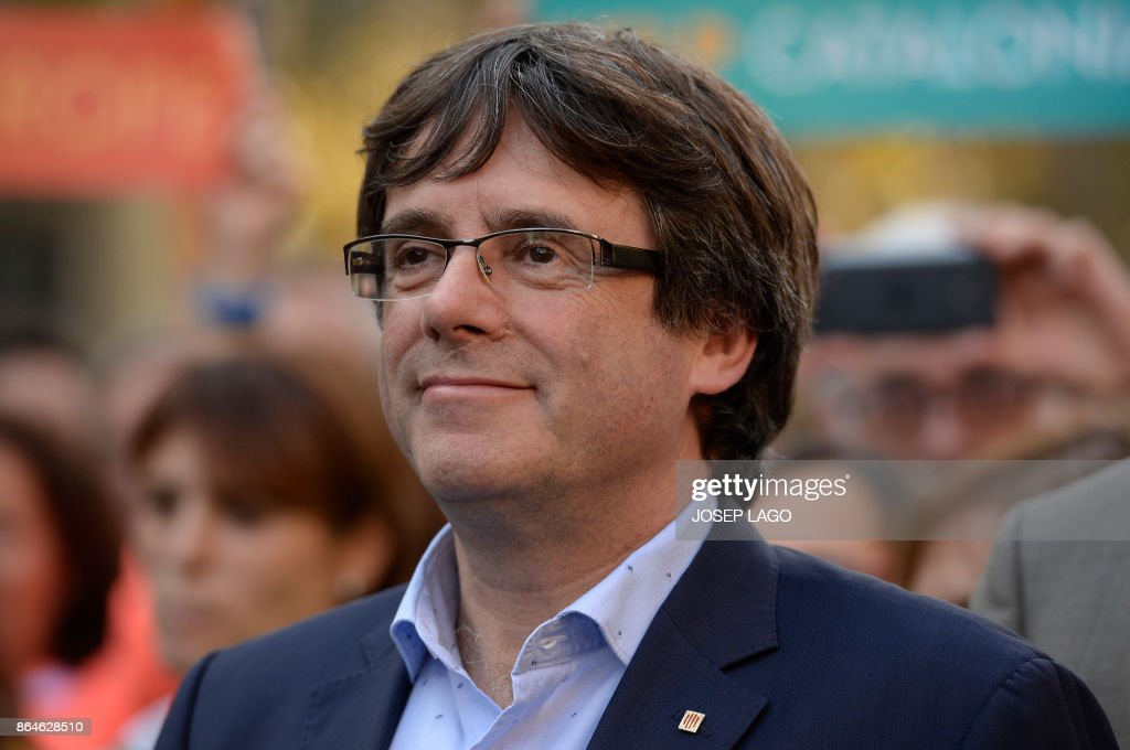 ?Catalan regional president Carles Puigdemont attends a demonstration on October 21, 2017 in Barcelona, to support two leaders of Catalan separatist groups, Jordi Sanchez and Jordi Cuixart, who have been detained pending an investigation into sedition charges. Spain announced that it will move to dismiss Catalonia's separatist government and call fresh elections in the semi-autonomous region in a bid to stop its leaders from declaring independence. / AFP PHOTO / Josep LAGO
