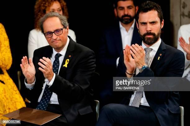 Catalan regional president Quim Torra and Catalan Parliament Speaker Roger Torrent applaud during the new Catalan regional government's swearingin...