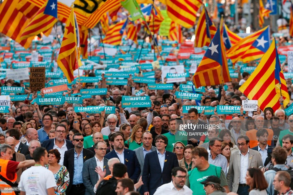 ?(Center) Catalan regional vice-president and chief of Economy and Finance Oriol Junqueras and Catalan regional president Carles Puigdemont attend a demonstration on October 21, 2017 in Barcelona, to support two leaders of Catalan separatist groups, Jordi Sanchez and Jordi Cuixart, who have been detained pending an investigation into sedition charges. Spain announced that it will move to dismiss Catalonia's separatist government and call fresh elections in the semi-autonomous region in a bid to stop its leaders from declaring independence. /