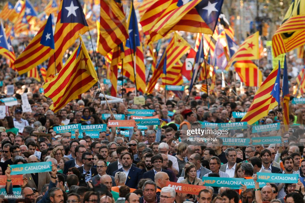 TOPSHOT - ?(Center) Catalan regional vice-president and chief of Economy and Finance Oriol Junqueras and Catalan regional president Carles Puigdemont attend a demonstration on October 21, 2017 in Barcelona, to support two leaders of Catalan separatist groups, Jordi Sanchez and Jordi Cuixart, who have been detained pending an investigation into sedition charges. Spain announced that it will move to dismiss Catalonia's separatist government and call fresh elections in the semi-autonomous region in a bid to stop its leaders from declaring independence. /