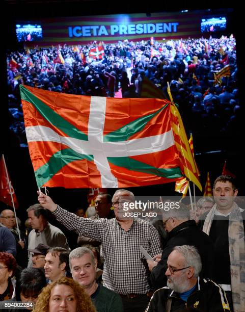 A Catalan Socialist party supporter waves an 'Ikurrina' during a campaign meeting for the upcoming Catalan regional election in Barcelona on December...
