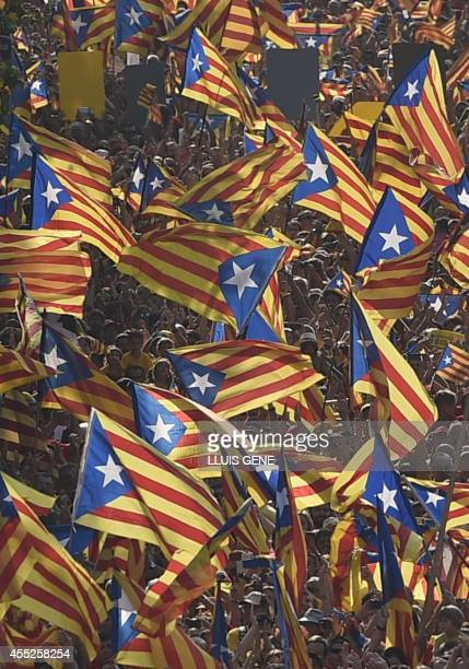 Catalans hold Catalan independentist flags during celebrations of Catalonia National Day in Barcelona on September 11 2014 Red and yellow flags...