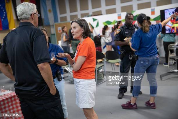 Catalina Horak head of the Building One Community immigrant center speaks with Stamford police officers during a communitybuilding event on August 10...