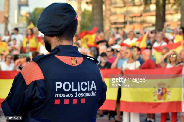 Catalonia police seen watching the counter protesters in favor of the unity of Spain waving national flags