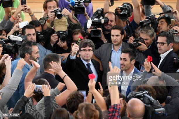Catalonia President Carles Puigdemont holds up a red flower after failing to vote in the referendum because of the Spanish police closing his polling...
