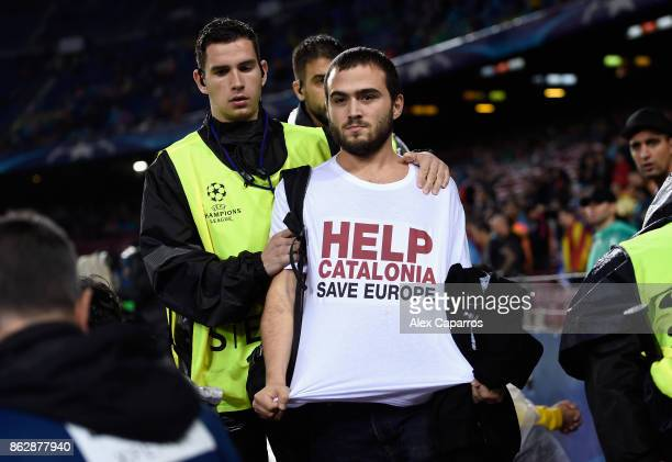 Catalonia protestor is taken away by stewards during the UEFA Champions League group D match between FC Barcelona and Olympiakos Piraeus at Camp Nou...