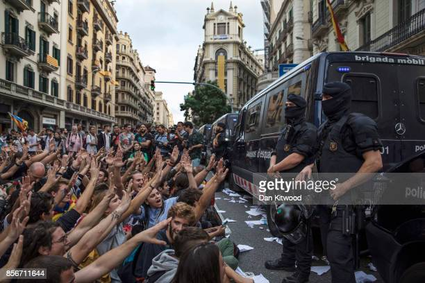 Catalonian police officers surround the 'General Direction of the National Police of Spain' offices of the Spanish National police as protesters...