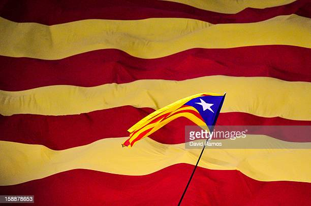 Catalonian proindepence flag flies overa Catalan flag prior to a friendly match between Catalonia and Nigeria at CornellaEl Prat Stadium on January 2...