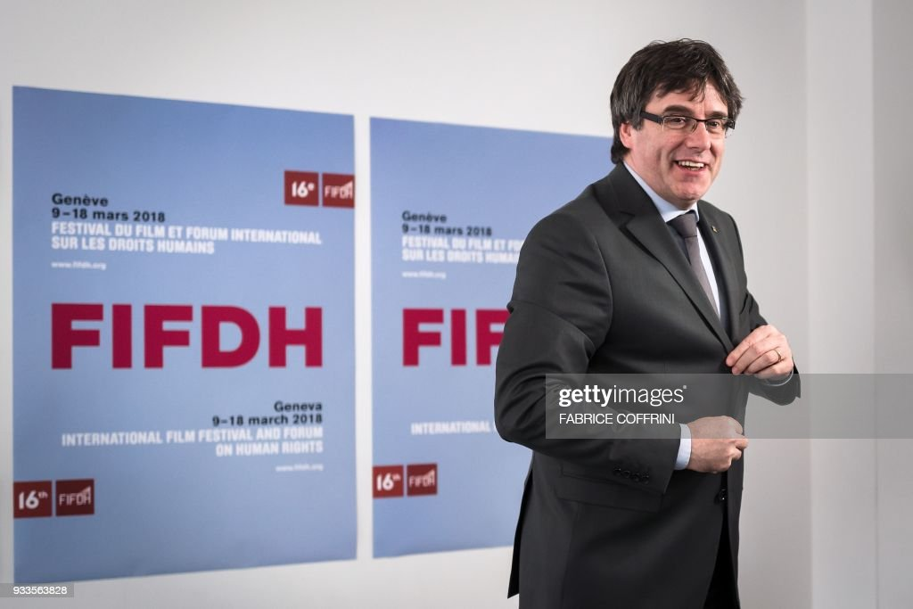 Catalonia's deposed leader Carles Puigdemont smiles as he leaves after giving an interview on the sideline of the International film festival and forum of the human rights (FIFDH) on March 18, 2018 in Geneva. Puigdemont said in an interview published on March 18, 2018 that he should have declared independence earlier, as delaying the call in hopes of starting dialogue with Madrid proved futile. / AFP PHOTO / Fabrice COFFRINI