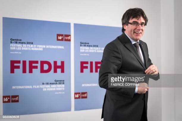 Catalonia's deposed leader Carles Puigdemont smiles as he leaves after giving an interview on the sideline of the International film festival and...