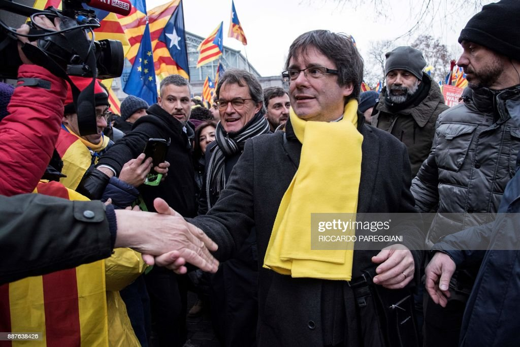 Catalonia's deposed regional president Carles Puigdemont (R) and Former Catalan regional president Artur Mas(C-L) shakes hands with supporters during a pro-independence demonstration on December 7, 2017 in Brussels. A sea of around 45,000 pro-Catalonia protesters demonstrated in Brussels on December 7 to show support for the region's deposed president Carles Puigdemont and urge the EU to support its drive for independence from Spain. / AFP PHOTO / Riccardo PAREGGIANI