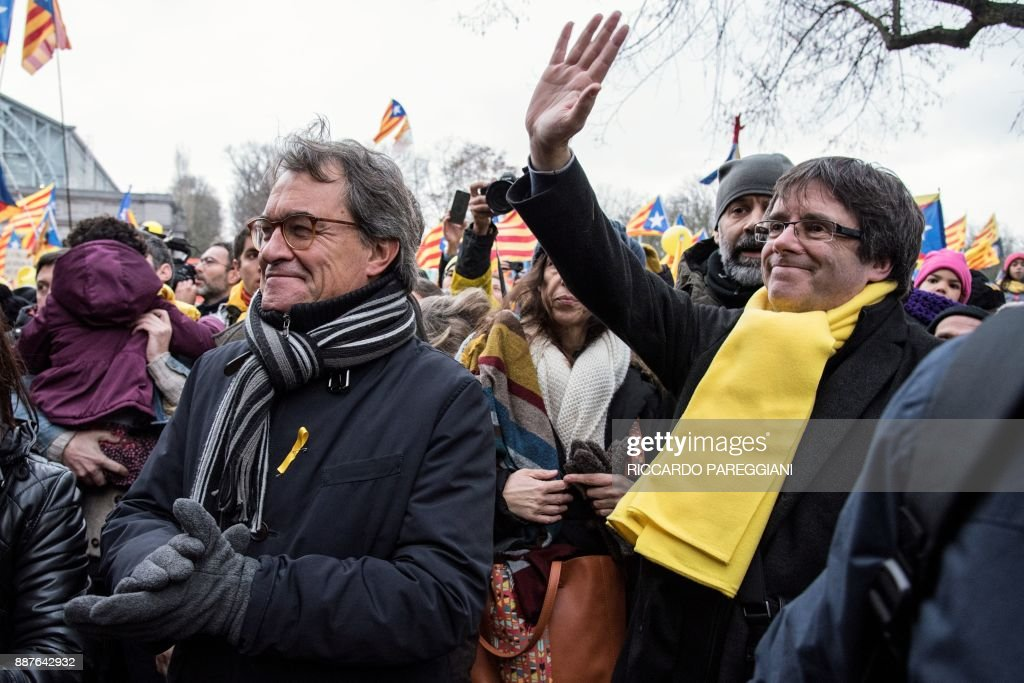 Catalonia's deposed regional president Carles Puigdemont (R) and Former Catalan regional president Artur Mas (L) wave to supporters during a pro-independence demonstration on December 7, 2017 in Brussels. A sea of around 45,000 pro-Catalonia protesters demonstrated in Brussels on December 7 to show support for the region's deposed president Carles Puigdemont and urge the EU to support its drive for independence from Spain. / AFP PHOTO / Riccardo PAREGGIANI