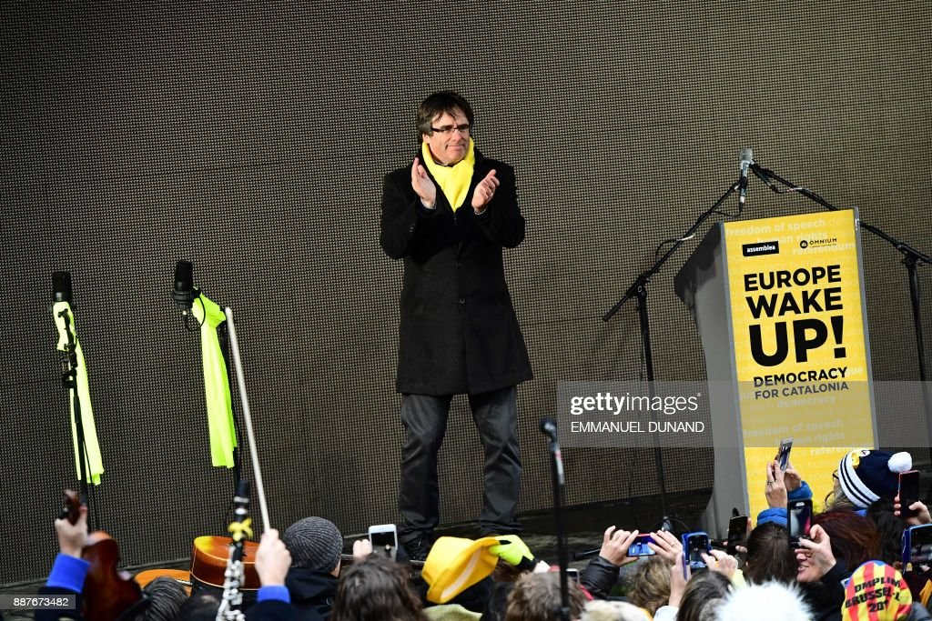 Catalonia's deposed regional president Carles Puigdemont arrives to deliver a speech during a pro-independence demonstration on December 7, 2017 in Brussels. A sea of around 45,000 pro-Catalonia protesters demonstrated in Brussels on December 7 to show support for the region's deposed president Carles Puigdemont and urge the EU to support its drive for independence from Spain. /