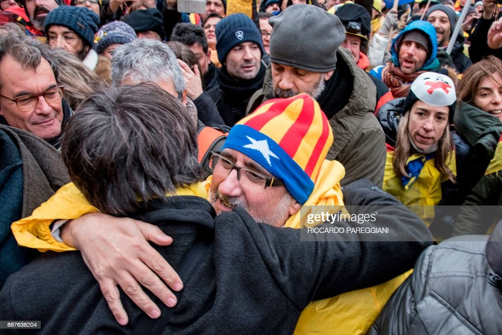 Catalonia's deposed regional president Carles Puigdemont (C) is greeted by supporters during a pro-independence demonstration on December 7, 2017 in Brussels. A sea of around 45,000 pro-Catalonia protesters demonstrated in Brussels on December 7 to show support for the region's deposed president Carles Puigdemont and urge the EU to support its drive for independence from Spain. / AFP PHOTO / Riccardo PAREGGIANI