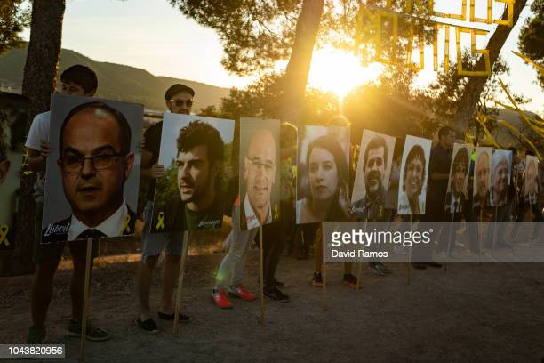 Catalonia's Independence supporters hold portraits of jailed and exiled separatist leaders as they gather on a field overlooking the prison of...