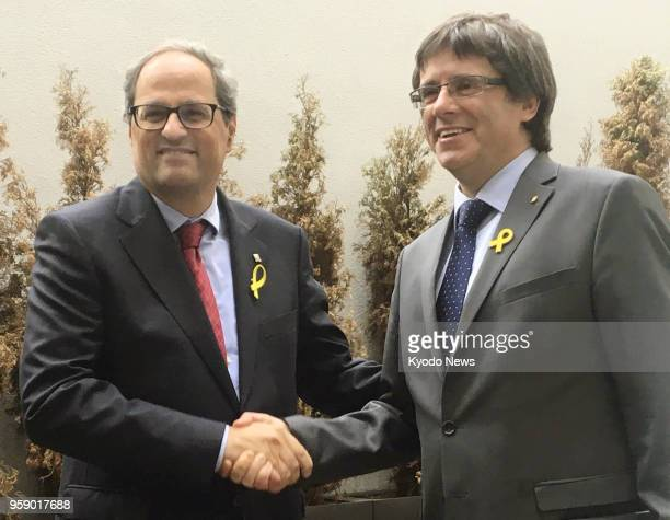 Catalonia's new leader Quim Torra and his predecessor Carles Puigdemont shake hands ahead of a press conference in Berlin Germany on May 15 2018...