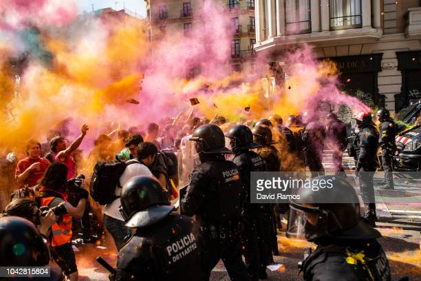 Catalonia's proindependence supporters clash with Mossos d'Esquadra police officers as they protest against a demonstration to commemorate their...