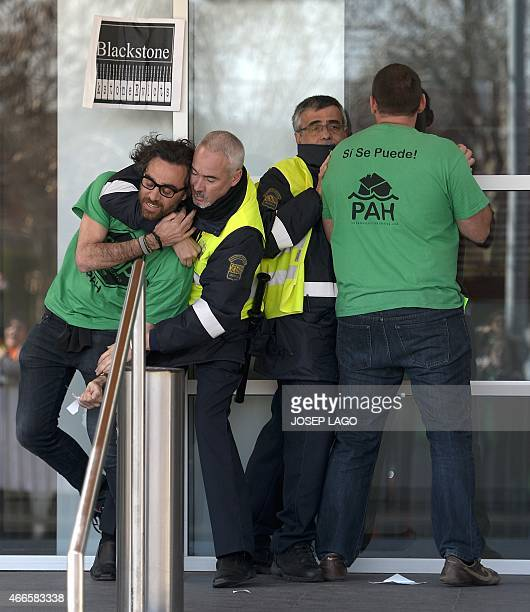 Catalunya Caixa Bank's security members block two demonstrators at the entrance of the bank's office during a demonstration against mortgage debt...