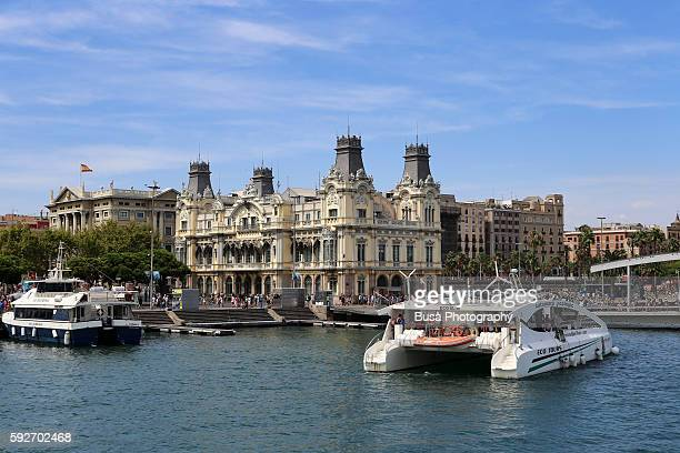 Catamaran approaching coastline, with old Customs building in the Port Vell (old port) of Barcelona, Spain