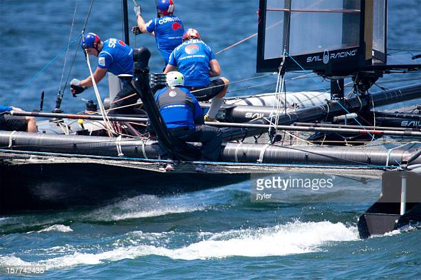 catamaran yacht racing crew hard at work. - catamaran stock photos and pictures