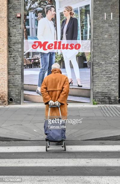 An elderly gentleman wearing gloves to protect himself from Coronavirus infection crosses the pedestrian crosswalk dragging the shopping cart with...