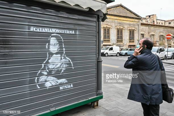 The work of street art arouses the curiosity of this citizen with the mask to protect himself from the coronavirus on March 21 2020 in Catania Italy...