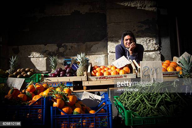 catania, sicily: fruit vendor at outdoor market - catania stock photos and pictures