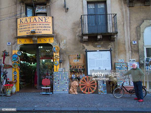 catania, sicily: senior with bike outside souvenir shop - catania stock photos and pictures