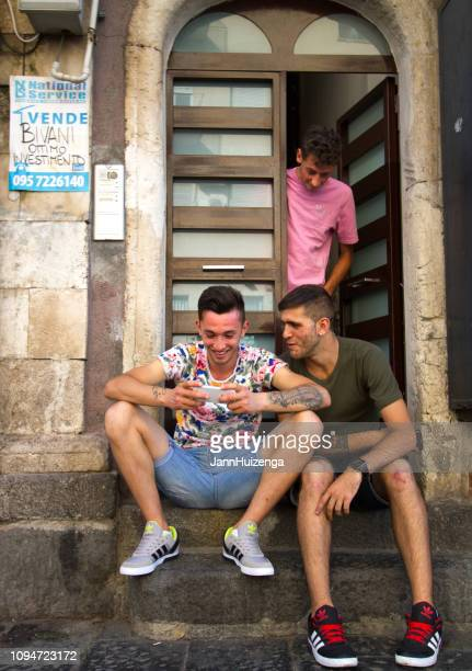 catania, sicily: young men relax on door stoop - legs spread open stock photos and pictures