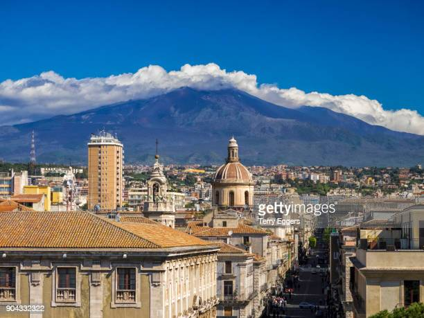 catania, the city center with mt. etna volcano covered with a layer of clouds in the background. - catania stock photos and pictures