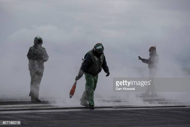 Catapult and arresting gear personnel a member of the flight deck recognised by their green attire runs through steam after a plane took off during...